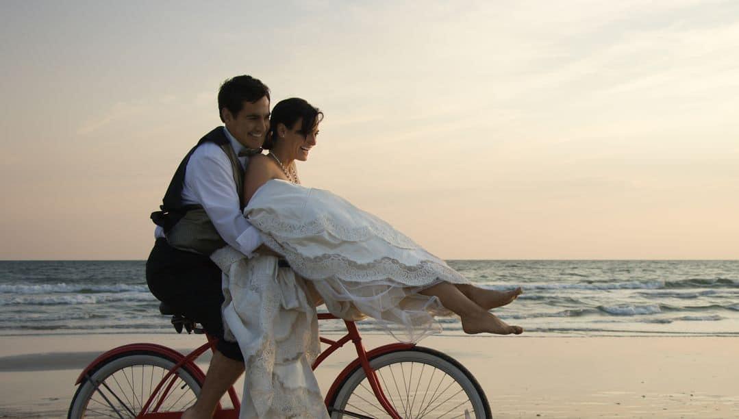 Brautpaar auf Fahrrad am Strand