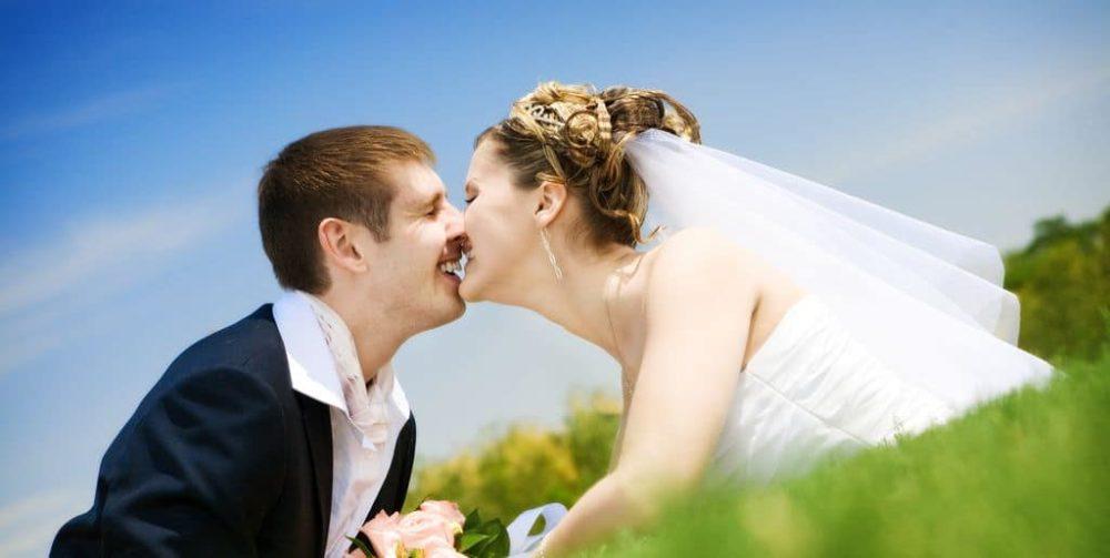 Küssendes Brautpaar im Gras