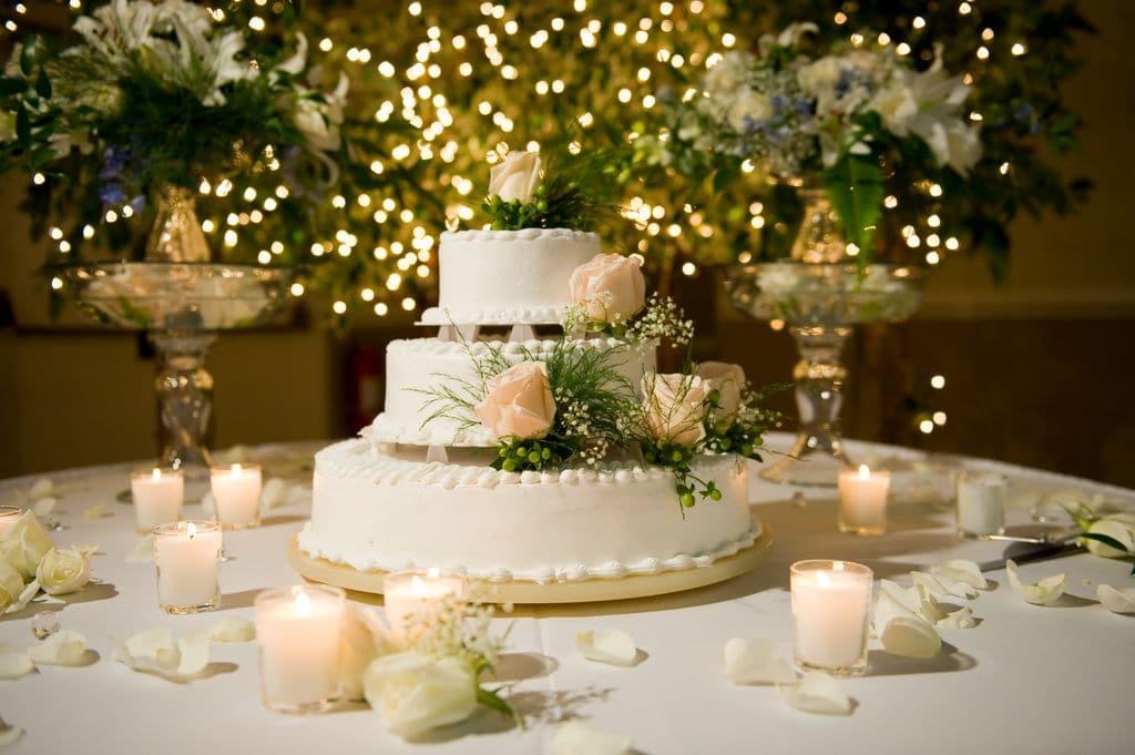 Hochzeitstorte auf Tisch dekoriert mit Windlichtern