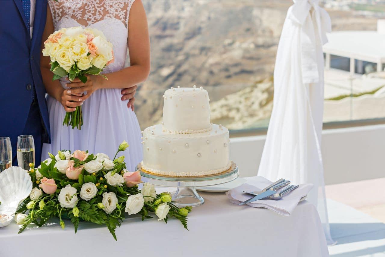 Hochzeitstorte auf dem Tisch und Brautpaar