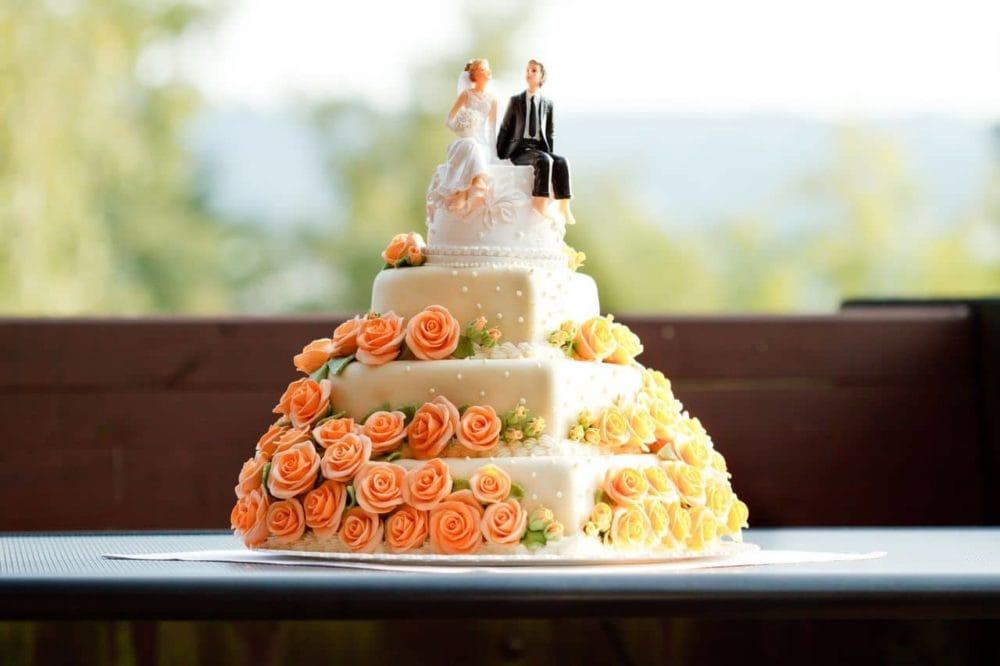 Hochzeitstorte mit Brautpaar mit Rosen