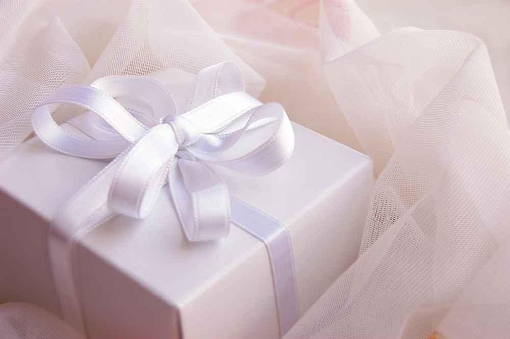 weißes Geschenk mit Band auf Tüll