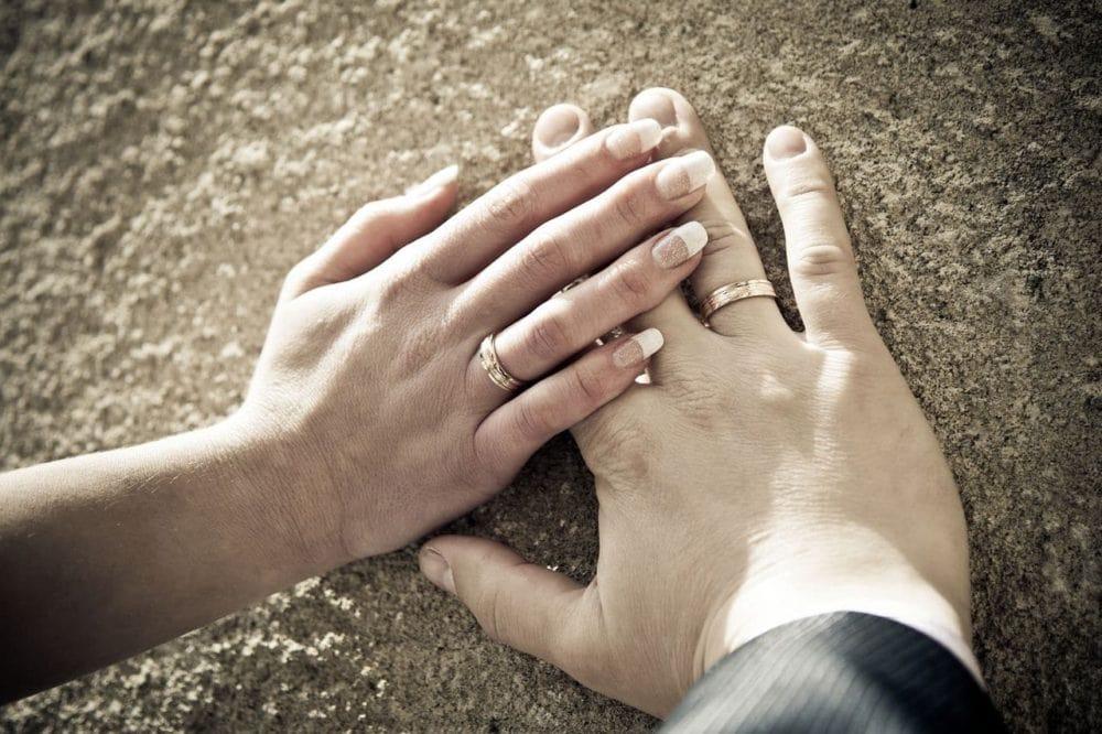 Hände des Brautpaares mit eheringen