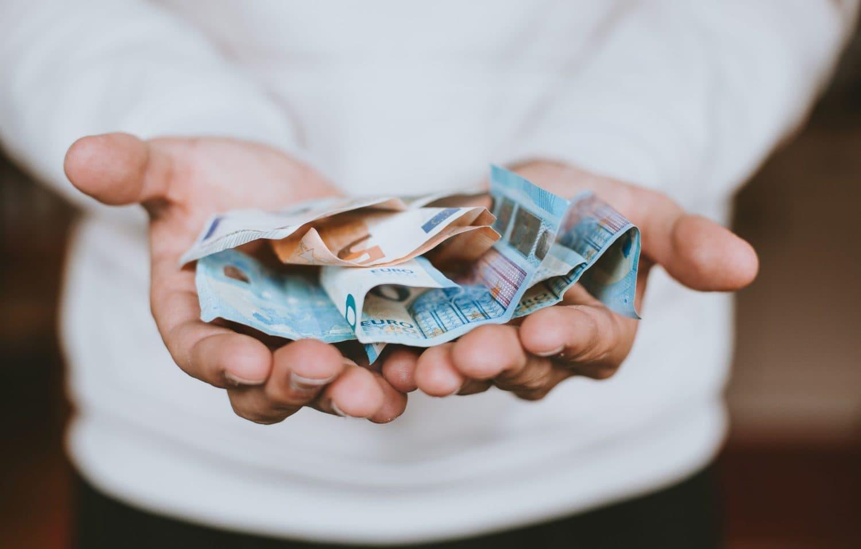 Jemand hält Geldscheine in den Händen