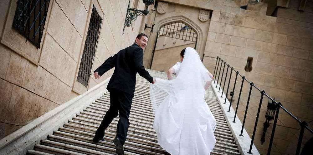 Brautpaar auf der Treppe eines Schlosses