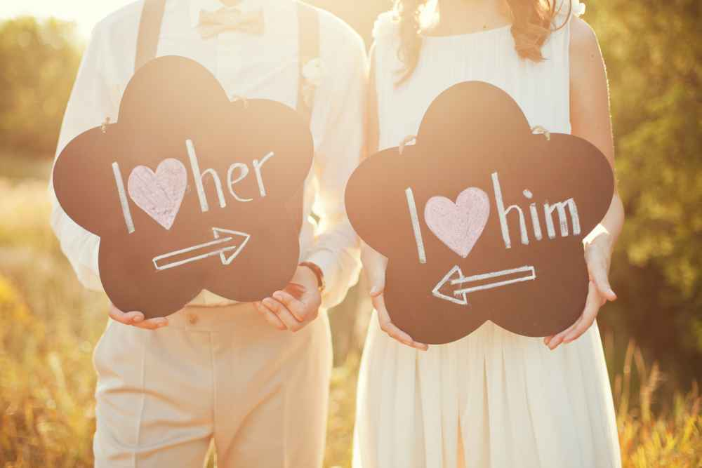 Brautpaar hält Schilder mit Liebesbotschaften