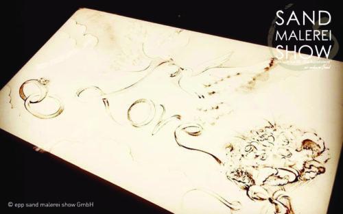 Ihre Liebesgeschichte in Sand gemalt